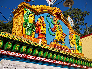 Bright, colorful figures decorate the top of a building in Bangalore, Karnataka, India.