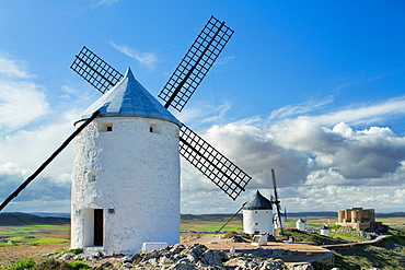 Typical windmill and castle in Consuegra village, in the Route of Don Qiuijote, Toledo province, Castilla-La Mancha, Spain.