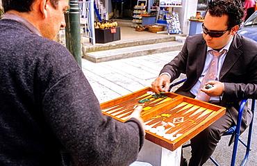 Friends playing Backgammon in Ploutarhou street. Kolonakia's district, Athens, Greece, Europe.