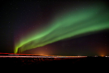Aurora Borealis over road by country farms, Iceland.