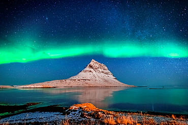 Aurora Borealis or Northern lights with the Milky Way Galaxy over fjord. Mt. Kirkjufell, Grundarfjordur, Snaefellsnes Peninsula, Iceland.