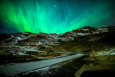 Aurora Borealis or Northern lights over geothermal area, Krysuvik-Seltun located on the Reykjanes Peninsula, Iceland. Wooden pathway to accommodate visitors.