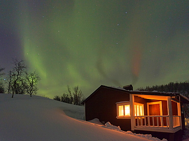 Northernlight, Aurora borealis, over a cottage with light coming through the window in winter season in march, in Riksgransen, Swedish lapland, Sweden.
