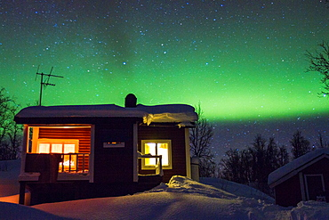 Cottage with northern light, aurora borealis in background in winter time at Riksgransen in swedish lapland.