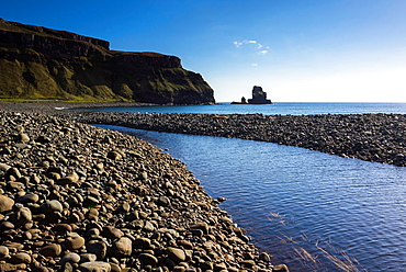 River Talisker reaching the boulder covered beach of Talisker Bay in the Scottish Highlands.