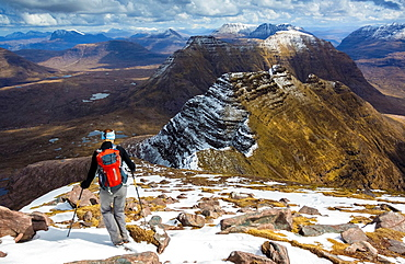 A hiker heading down Ben Alligin in the bright sun towards the three horns on the that are in still in the shade of the clouds.