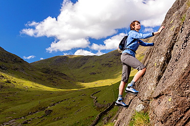 Female rock scrambler climbing up Seathwaite Slabs, Lake District, UK.