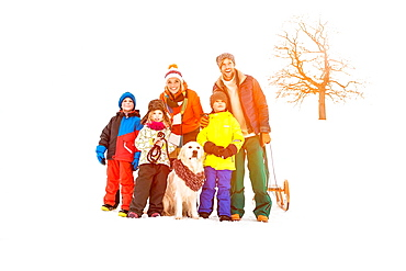 Family with three children standing in snow