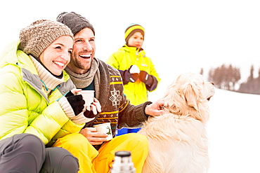 Man and woman with hot drinks and dog, son in background