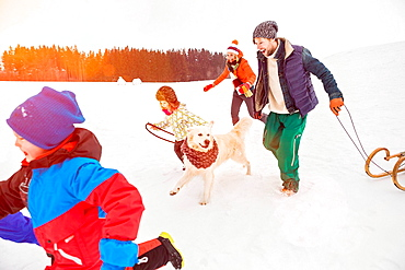 Family running in snow with dog