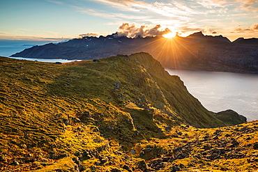 Sun setting behind mountains of Flakstadoy from Skottind, VestvÂgoya, Lofoten islands, Norway