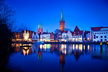 Nightfall in Lubeck, to the other side of the river Trave. Highlighting the towers of the Church of Santa Maria, and the tower of St Petry. Lubeck, Schleswig-Holstein, Germany.