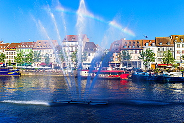 Jet of water and Quai des Pecheurs, fishermen quay with barges on Ill river and waterfront houses Strasbourg Alsace France.