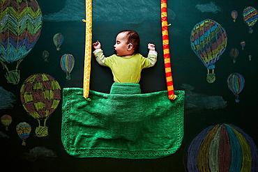 Baby girl sleeping against drawings on blackboard, overhead view