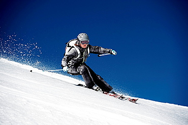 Female skiing at speed down mountain