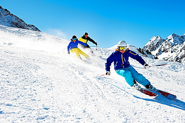 Three skiers going downhill