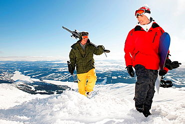Snowboarders and skiers carrying equipment to the top of mountain