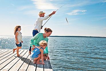 Family fishing off pier, Utvalnas, Sweden
