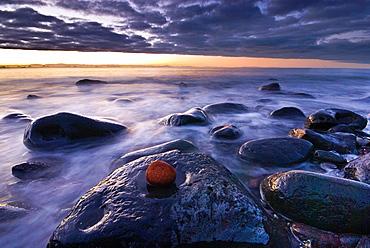 Sunset over rocky coast line, Sumner beach, Christchurch, New Zealand.