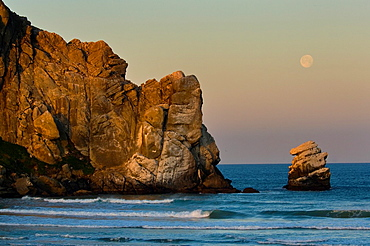 Full moon sets at dawn over the base of Morro Rock and the Pacific Ocean, Morro Bay, California.