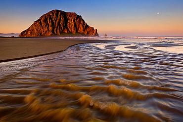 Sunrise light on Morro Rock over Little Morro Creek, Morro Strand State Beach, Morro Bay, California.