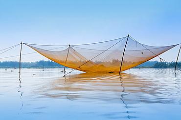 Large fishing nets in the Thu Bon River near Hoi An, Vietnam, Asia.