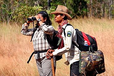 Tour guide leading a group of tourists. Dey Ei Trek to the Chbar river. Mondulkiri, Cambodia.