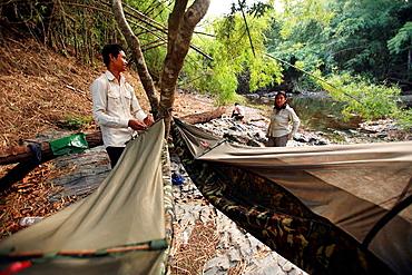 Guide helping tourists to set up camp along the O Chbar river. Dey Ei Trek, Mondulkiri, Cambodia.