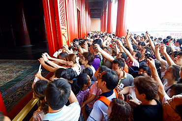 Crowd of tourists photographing the emperor throne in the Forbidden City, Beijing, China.