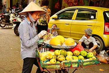 Mango and melon vendor in Hanoi, Vietnam.