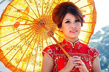 Chinese woman in traditional cheongsam outfit. Image taken at Sarawak Museum, Kuching, Sarawak, Malaysia.