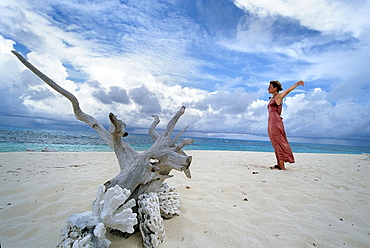young woman relaxing on a beach of Denis island, Republic of Seychelles, Indian Ocean