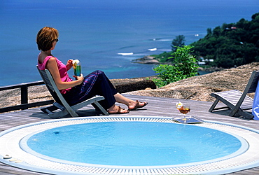 young woman sitting by a jacuzzi at the Le Chateau de Feuilles luxury hotel, Praslin island, Republic of Seychelles, Indian Ocean
