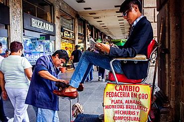 Shoeshine man and client, in Plaza de la Constitucion,El Zocalo, Zocalo Square, Mexico City, Mexico.