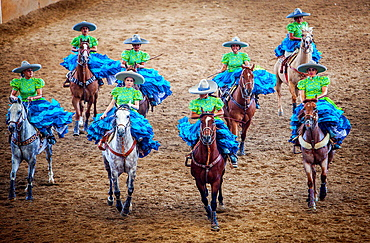 Escaramuzas ride their horses. A charreada Mexican rodeo at the Lienzo Charro Zermeno, Guadalajara, Jalisco, Mexico.
