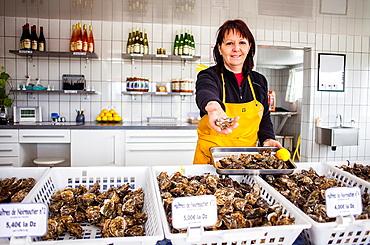 shopkeeper of Shop at oyster farm selling oysters on Port du Bonhomme a La Gueriniere, ile de Noirmoutier, La Vendee, Pays de la Loire, France