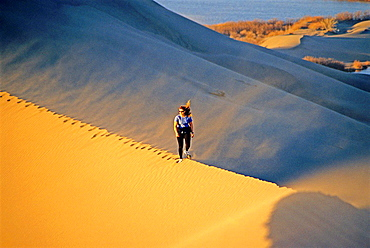 hiking the Bruneau Dunes during sunset at Bruneau Dunes State Park near the town of Bruneau in southern Idaho.