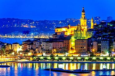 Europe, France, Alpes-Maritimes, Menton. Basilica Saint Michel and the marina at night.