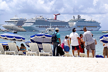 Visitors on Great Bay beach Philipsburg with three cruise ships docked in background St Maarten