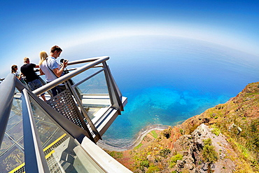 Tourist on the panoramic terrace at the top of Cabo Girao (580 m highest) cliff, Camara de Lobos, Madeira, Portugal.