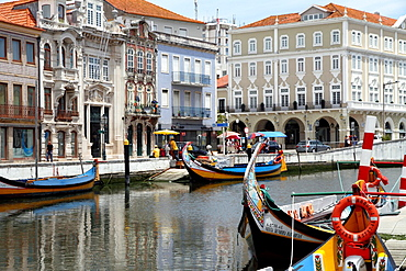 Portugal, Aveiro. Moliceiro boats docked by Art Nouveau style buildings along the central canal.