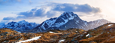 Stornappstind (740m) mountain peak rises above dramatic landscape, viewed from Offersoykammen, Lofoten Islands, Norway.