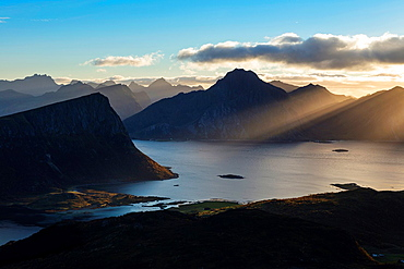 Rays of light shine over mountains and Nappstraumen from summit of Holandsmelen mountain peak, Vestvagoy, Lofoten Islands, Norway.