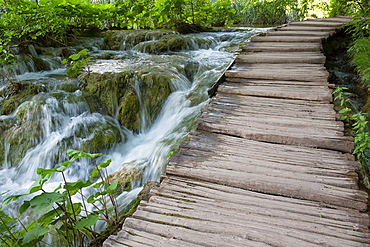 wooden pathway and stream with waterfalls, Plitvice Lakes National Park, Croatia.