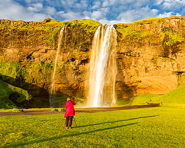 Woman taking pictures of Seljalandsfoss Waterfall, Iceland.
