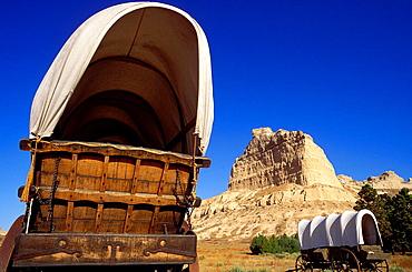 Conestoga wagons under Eagle Rock on the Oregon Trail, Scotts Bluff National Monument, Nebraska USA.