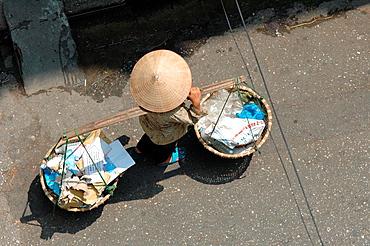 woman carries baskets on shoulder in Hanoi, Vietnam