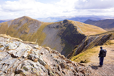 Hiker taking in the view of Hobcarton valley from Hopegill Head with Grisedale Pike in the distance. The Lake District.
