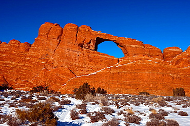 Skyline Arch on a winter afternoon with snow on the ground, Arches National Park, Utah, United States of America.
