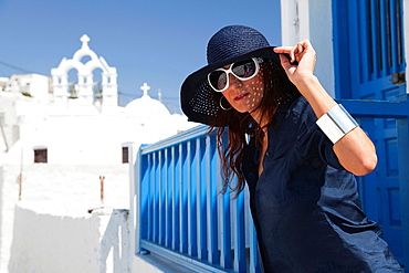 Woman posing in front of a church, Amorgos, Cyclades Islands, Greek Islands, Greece, Europe.